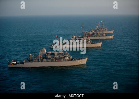 161206-N-ZV163-0371  ARABIAN GULF (Dec. 6, 2016) The Avenger class mine countermeasure (MCM) ships USS Dextrous (MCM 13), USS Gladiator (MCM 11), USS Devastator (MCM 6), and USS Sentry (MCM 3), part of Commander, Task Force (CTF) 52, sail in formation as part of a photo exercise in the Arabian Gulf. The combined MCM force enhances mine-hunting capabilities in searching, identifying and neutralizing mines threatening the freedom of navigation and the free flow of commerce. (U.S. Navy photo by Petty Officer 2nd Class Christina Brewer/Released) - Stock Photo