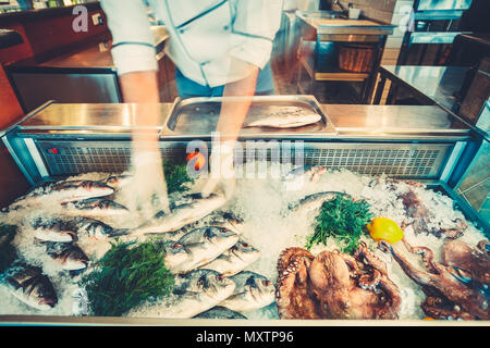 The chef-cooker is taking the freshly caught fish out of the refrigerated counter for the cooking delicious meal in the restaurant. Fresh seafood the fish and octopuses for healthy lifestyle. - Stock Photo