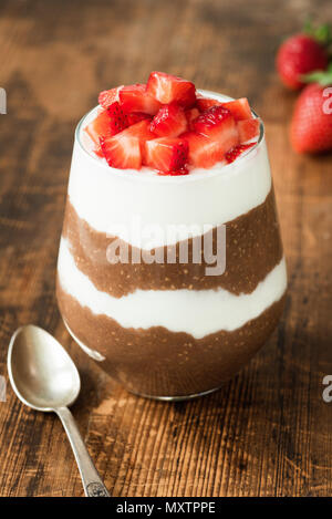 Chia pudding with yogurt, chocolate and strawberries in a glass on wooden table. Closeup view, selective focus - Stock Photo