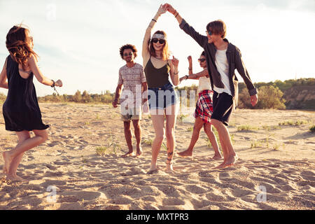 Image of happy cheerful young loving couples friends walking outdoors on the beach dancing. - Stock Photo