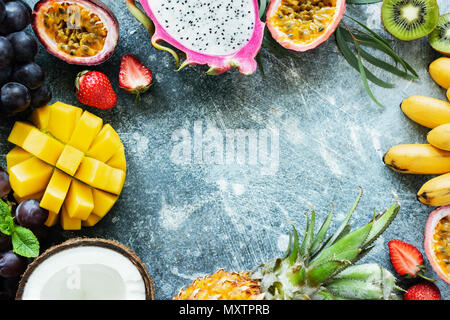 Frame of fresh tropical fruits on concrete background with copy space for text, top view. Concept of summer, exotic fruits, vegan and paleo diet - Stock Photo