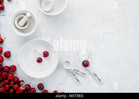 Cherries and white porcelain baking dishes with measuring spoons on a white stone background. Minimalist cherry pie baking concept. - Stock Photo
