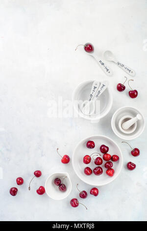 Minimalist cooking concept with red cherries and porcelain baking dishes on a white stone background. White on white flat lay with copy space. - Stock Photo