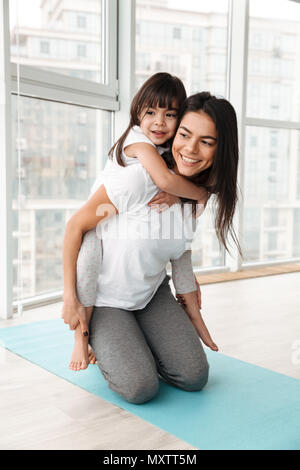 Photo of cheerful family mother and child having fun while woman piggybacking her daughter indoor - Stock Photo