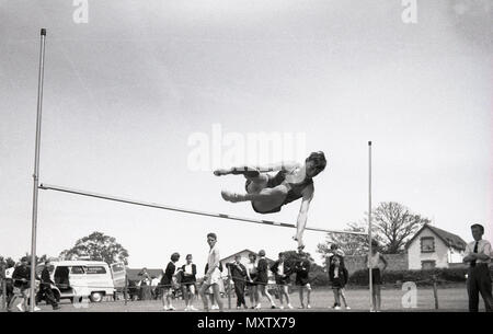 1960, historical picture of secondary schoolboy doing the high jump event at a inter-school county sports day, Dorset, England, UK. - Stock Photo