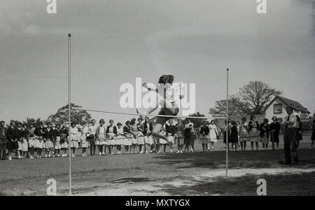 1960, historical picture of secondary schoogirl taking part in an inter-school county sports day, Dorset, England, UK. Here we see her doing the high jump with a rather individual style watched by a line of spectatotrs. - Stock Photo