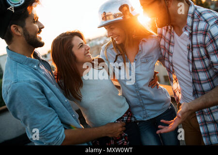 Young people partying on terrace with drinks at sunset - Stock Photo