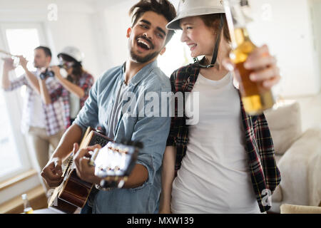 Group of happy young friends having fun and drinking beer - Stock Photo