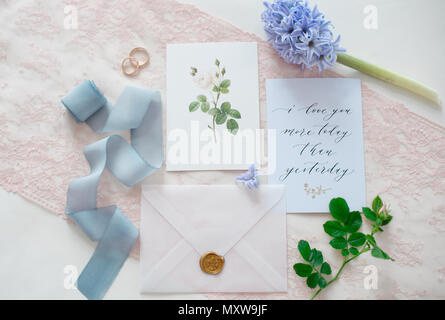 wedding invitation card as a decorated letter with flowers and ribbons top view - Stock Photo