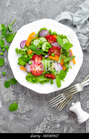 Salad. Fresh vegetable salad with tomato, onion, cucumbers, pepper, lettuce and green peas. Vegetarian salad with vegetables on plate - Stock Photo