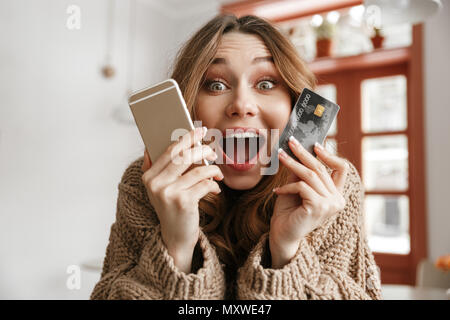 Happy emotional woman 20s holding credit card and mobile phone,while resting in cafe - Stock Photo