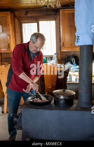 Ontonagon, Michigan - John West cooks dinner on a wood stove in a backpackers' cabin in Porcupine Mountains Wilderness State Park. The park maintains  - Stock Photo