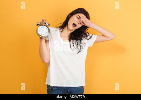 Image of young sleepy woman isolated over yellow background holding alarm clock yawning. - Stock Photo