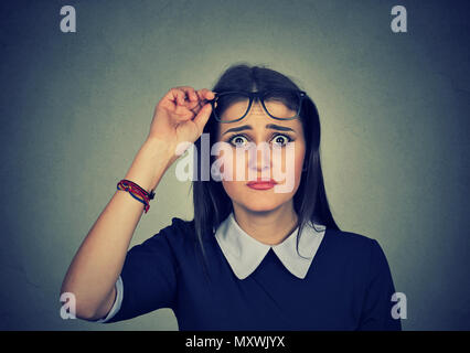 Pretty young woman taking off glasses and looking at camera in question having problems with understanding - Stock Photo