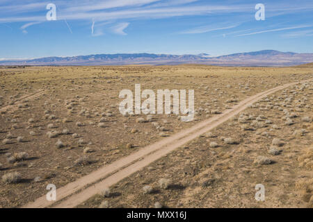 Dirt road track in the dry arid plains of central California on the border of the Mojave desert. - Stock Photo