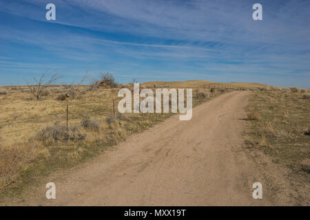 Barbed wire fence borders a dirt road in the wilderness of southern California Mojave Desert. - Stock Photo