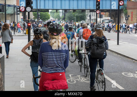 A large number of cyclists at traffic lights during the morning rush hour in central london. Commuting to work on bicycle in the capital city traffic. - Stock Photo