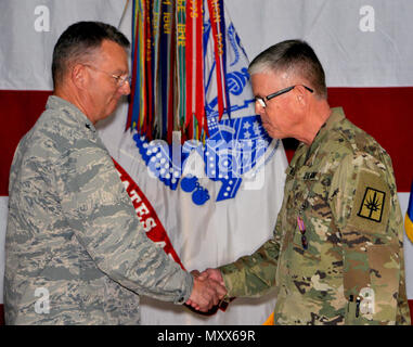 Maj. Gen. Anthony German, the adjutant general of New York (left), congratulates Chief Warrant Officer 5 Robert Wold, the outgoing command chief warrant officer of the New York Army National Guard (right), after awarding him the New York State Conspicuous Service Medal during a change-of-authority ceremony at New York National Guard headquarters here on Dec. 9. Chief Warrant Officer 4 Jeffrey Schirmer took over command chief warrant officer duties during the ceremony. Schirmer, a Leicester N.Y. resident and a veteran of two wars, will be responsible for recruiting warrant officers to fill the  - Stock Photo