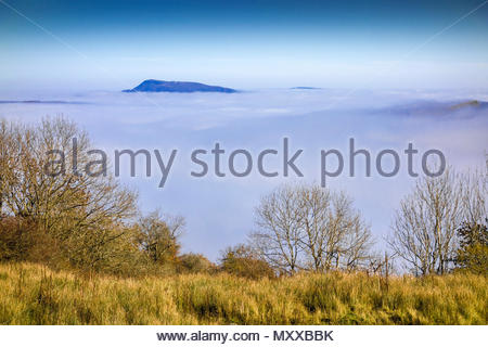 Fog caused by temperature inversion fill the River Usk valley. The peak of Great Skirrid (Big Skirrid) is in the distance; Monmouthshire, Wales, UK. - Stock Photo