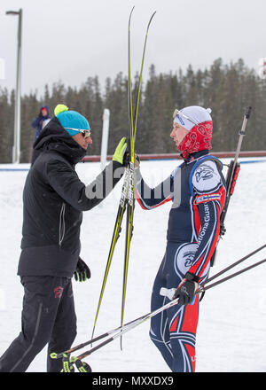 Alaska Army Guardsman Pfc. Travis Cooper, a construction equipment mechanic with the 207th Engineer Utility Detachment, gives a high-five to Vermont Air National Guardsman Tech. Sgt. Travis Voyer, an assistant coach with the National Guard Biathlon development team, after claiming his second gold in the junior men's 12.5 km mass start in the North American #1 and Calforex #1 Biathlon Cups at the Canmore Nordic Centre Provincial Park in Canmore, Alberta, Dec. 4, 2016. Cooper, 20, of Kenai, also took first place in the junior men's 10 km sprint the day before. Cooper trains year-round and compet - Stock Photo