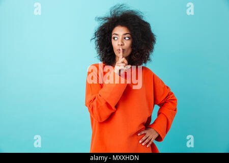 Image of african woman 20s in casual clothing holding index finger on lips and asking to keep silence isolated over blue background - Stock Photo