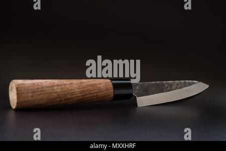wooden knife on a black leather surface closeup - Stock Photo