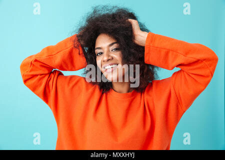 Portrait of satisfied woman in red shirt posing on camera and holding hands at head isolated over blue background - Stock Photo