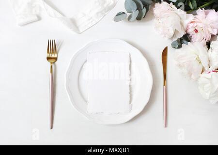 Feminine wedding, birthday desktop mock-up scene. Porcelain plate, blank craft paper greeting cards, silk ribbon, golden cutlery, eucalyptus, peony fl - Stock Photo