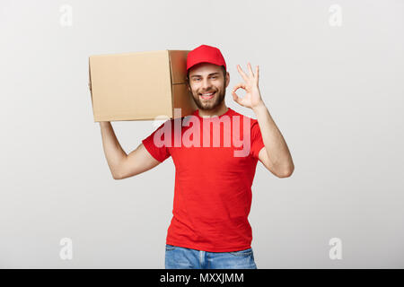 Cheerful young delivery man in red cap standing with parcel post box isolated over white background showing okay sign gesture. - Stock Photo