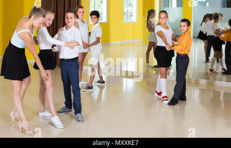 Teacher is showing to children how to dance tango in class. - Stock Photo