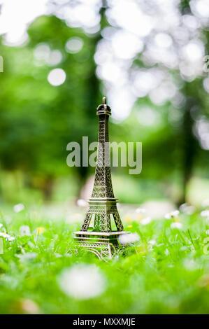 Eiffel tower miniature on the grasses - Stock Photo