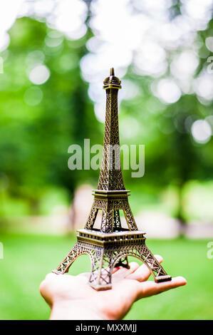 Hand holding Eiffel tower miniature - Stock Photo