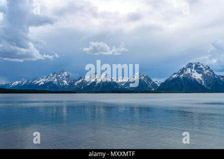 Stormy Mountain Lake - Spring afternoon storm clouds moving over Jackson Lake, with Teton Range rising in background, Grand Teton National Park, USA. - Stock Photo