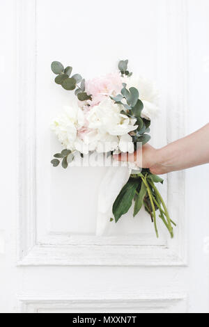 Styled stock photo. Feminine wedding, birthday composition. Closeup of woman's hands holding peonies flowers and eucalyptus bouquet, white vintage doo - Stock Photo