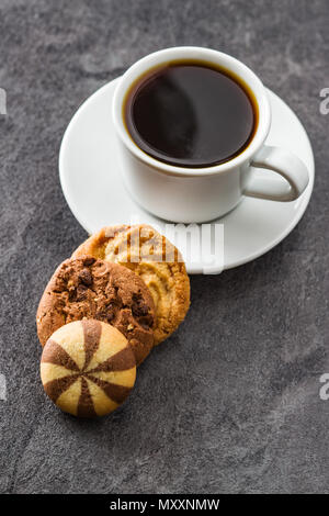 Cup of coffee and sweet cookies on black table. - Stock Photo
