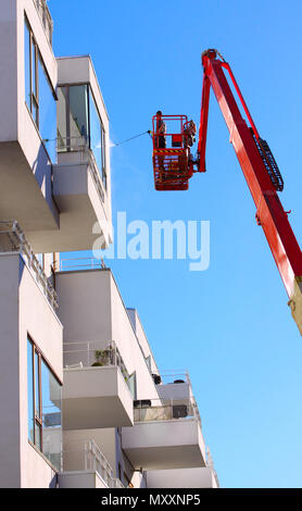 Man cleaning facade of a modern minimalistic apartment building on a telescopic boom lift using pressure jet wash with blue sky background - Stock Photo