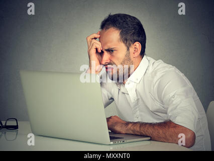 Annoyed man working at table and looking at laptop with anger having problems with gadget - Stock Photo