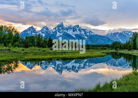 Sunset Teton Range at Snake River - Spring sunset view of Teton Range reflecting in calm Snake River in Grand Teton National Park, Wyoming, USA. - Stock Photo
