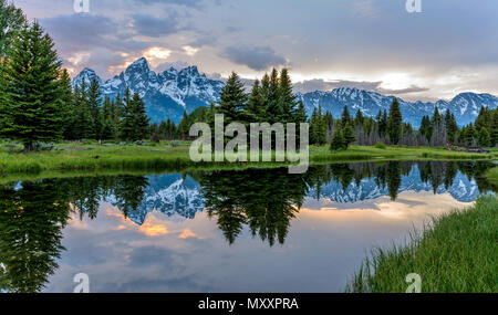 Teton Range and Snake River at Dusk - A cloudy spring evening view of Teton Range reflecting in calm Snake River in Grand Teton National Park, Wyoming. - Stock Photo