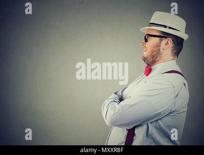 Side view of a chubby happy man in elegant outfit with bow tie and straw hat looking away confidently - Stock Photo