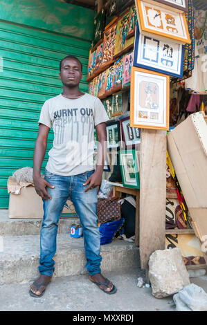 Young African male street vendor selling art pieces in the market. Abidjan, Ivory Coast, Circa May 2013. - Stock Photo