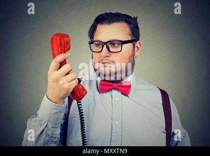 Formal chubby man in bow tie and glasses looking at handset in doubt and misunderstanding on gray - Stock Photo