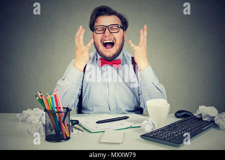 Stressed business man sitting at working place in chaos and yelling in frustration under pressure of time and workload - Stock Photo