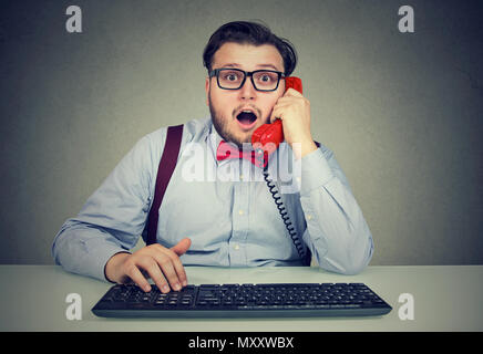 Chunky man in bow tie having shocking news on the phone while sitting at working table with computer - Stock Photo
