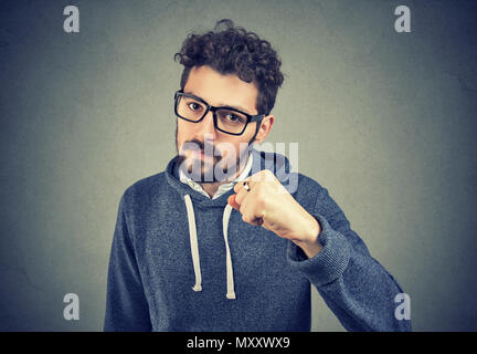 Bearded young man in glasses holding fist up looking serious and with threat on gray background. - Stock Photo