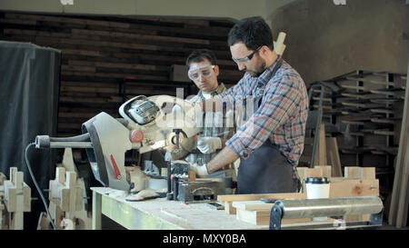 Two carpenters works on woodworking machine in workshop. - Stock Photo