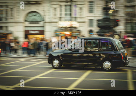 London, UK - October 2017. Taxi in Piccadilly Circus. Black cabs are the most iconic symbol of London as well as Red Double Decker Buses. - Stock Photo
