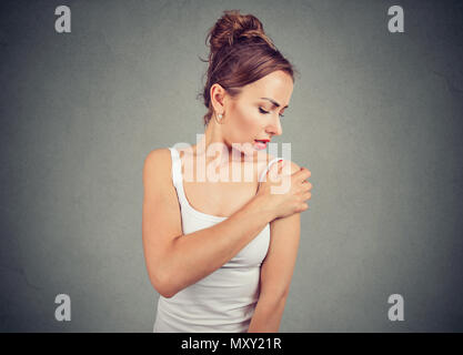 Young frowning girl in white tank top touching hurtful shoulder with expression of pain on gray background - Stock Photo