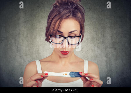 Young woman shocked cannot believe her eyes while checking positive pregnancy test - Stock Photo