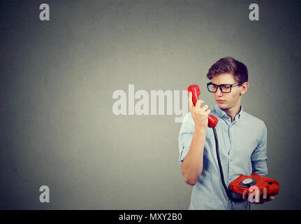 Casual young man in glasses having call on old-fashioned phone and looking confused while speaking - Stock Photo